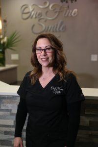 smiling dentist in glasses